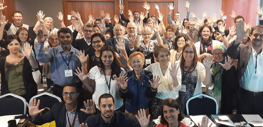 Rare Diseases International members raise their hands together